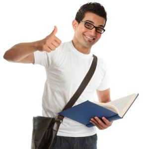 An excited happy university or college student, holding a text book and with thumbs up approval success, hand sign gesture. White background.